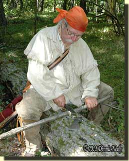 Notching the handle blank while sitting on an oak log.