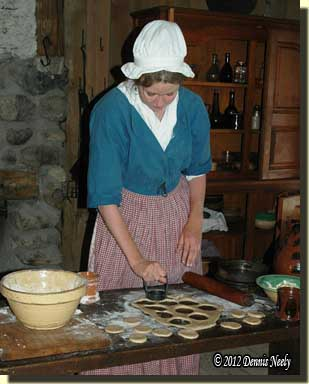 Eighteen-century woman cutting dough for blackberry tarts.