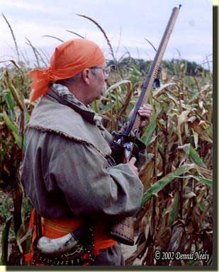 A traditional woodsman at the edge of a cornfield.