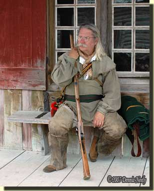 Dennis sitting on a bench in front of the guard house.