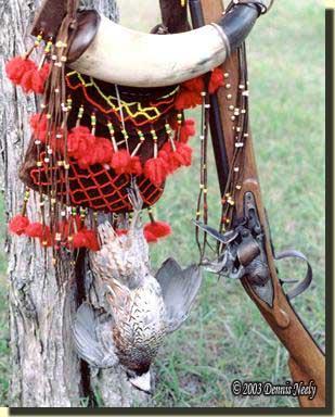 A bobwhite quail, a shot pouch, powder horn and Northwest trade gun.