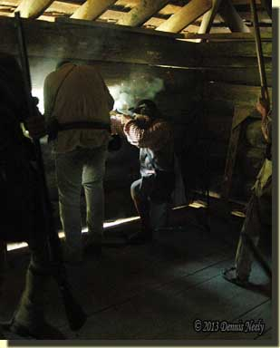 A woodsman fires through the gun port while others load.