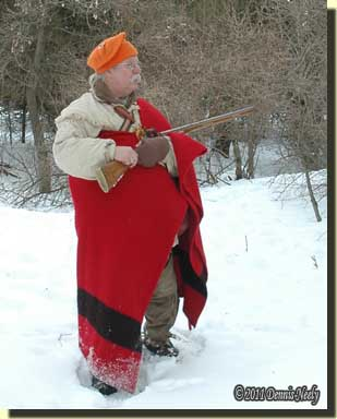 A traditional woodsman wearing a four-point trade blanket.