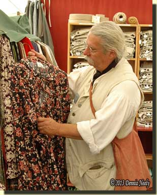 A traditional woodsman looking at a trade shirt on a merchant's rack.