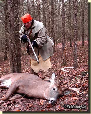 Tami Neely approaches a downed whitetail buck.