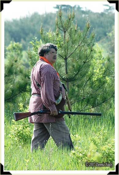 A traditional black powder hunter watches his dog work a pine grove.