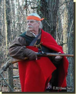 A traditional woodsman, clad in a trade blanket, looks back.