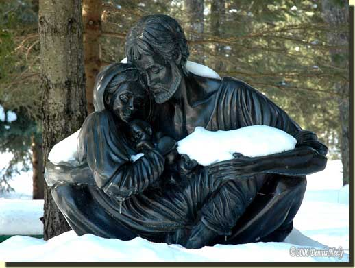 A sculture of the Holy Family covered with snow.