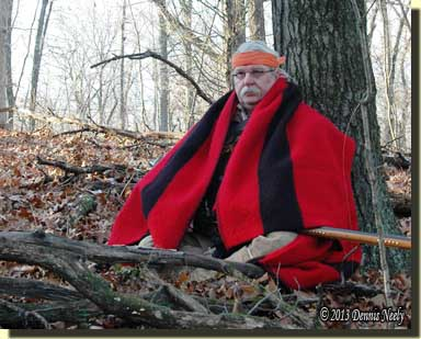 A traditional woodsman wrapped in a scarlet trade blanket sits against a red oak tree.