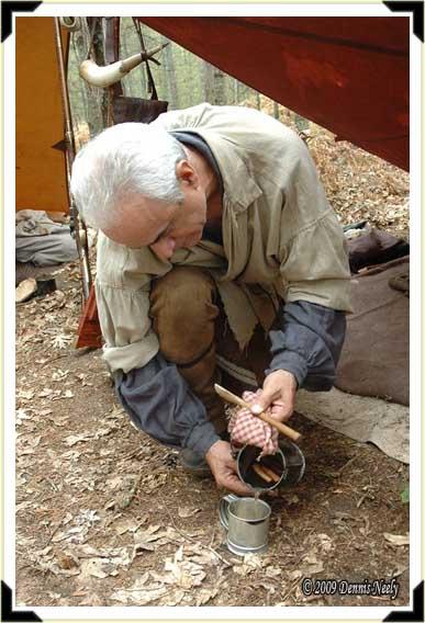 A traditional hunter pours sassafras tea into a tin cup.