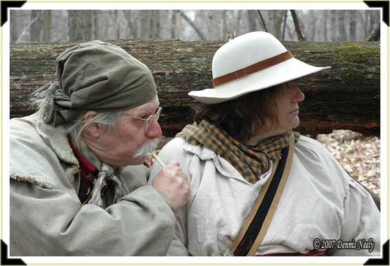A traditional woodsman clucks on a single wing-bone call while his wife watches.
