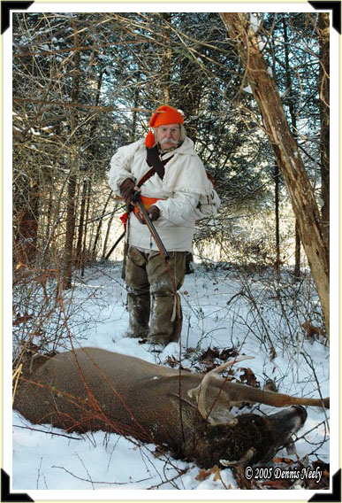 A traditional woodsman approaches a downed white-tailed buck.