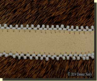 White glass bead edging on a buckskin strap.