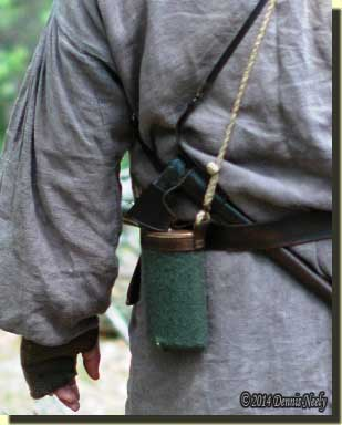 A copper canteen on a woodsman's hip.