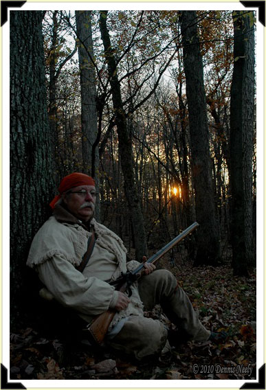A traditional woodsman sitting with his back against an oak tree.