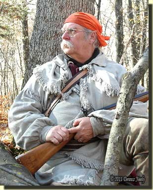 A tradtional woodsman sitting against an oak tree, watching for fox squirrels.