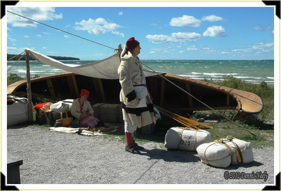 A French Canadian voyageur looks our over a choppy Straits of Mackinac