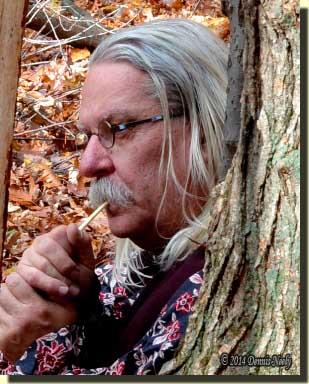 A traditional woodsmanmaking a turkey cluck with a wing-bone call.