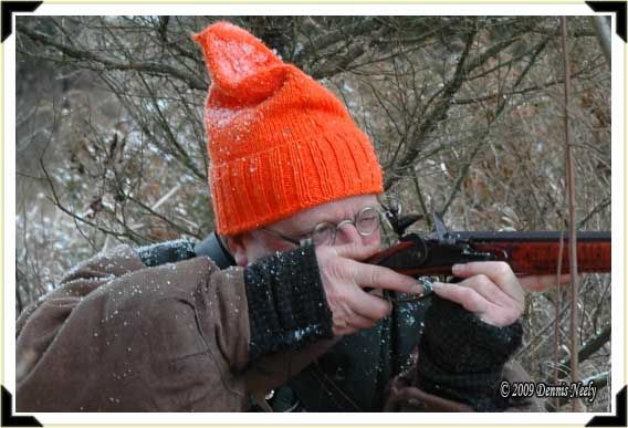A traditional woodsman aiming his flintlock rifle.