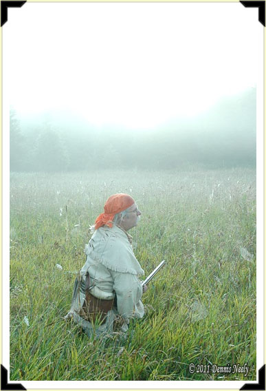 A traditional hunter kneeling in the grass on a foggy morning.