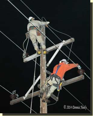 Two linemen climb a pole to begin replacing it.