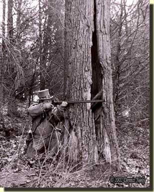 A traditional woodsman behind a lightning-split red oak tree.