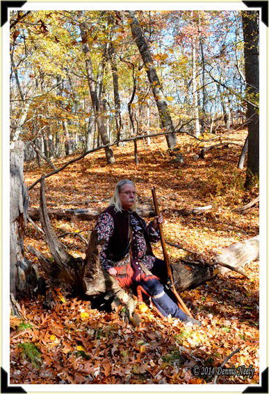 A traditional woodsman sitting on a log on a warm fall afternoon.