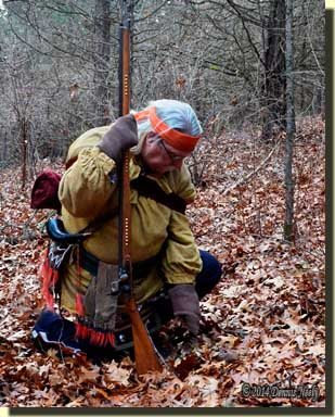 A traditional woodsman brushing leaves from a doe trail.