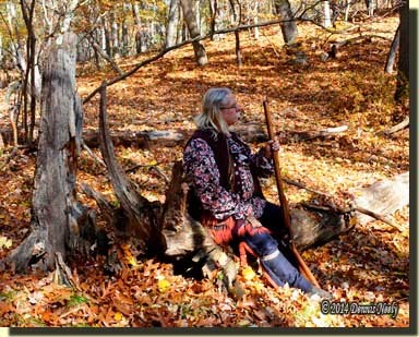 A traditioinal woodsman sitting on a log in the woods.