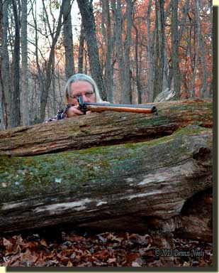 A traditional woodsman rests a Northwest gun over a downed log.