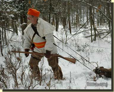A traditional woodsman dragging a deer with a portage collar.