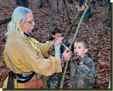 Two grandsons learn to lash saplings to the wigwam.