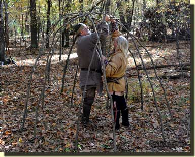 Two traditional woodsman building a wigwam.