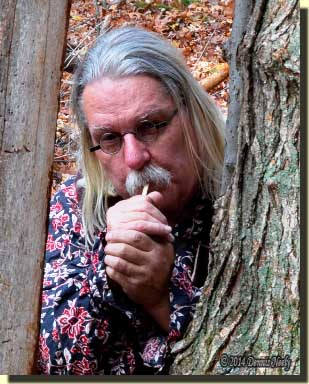 A traditional woodsman clucking on a single wing bone call.