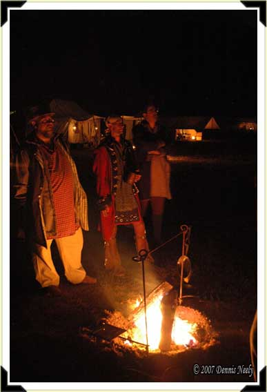 Three traditional hunters standing beside a campfire at night.