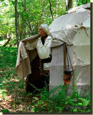 A traditioinal woodsman pushes away the wigwam's flap.