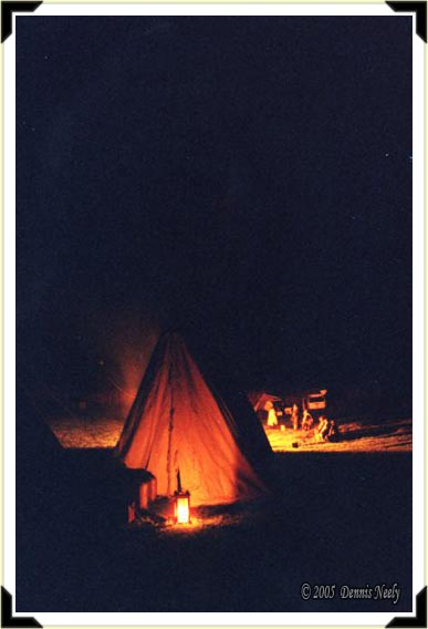 Candle light illuminates a wedge tent at night.