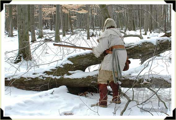 A French woodsman crouching behind a downed tree limb.