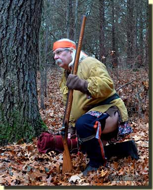 A traditional woodsman dropping to one knee while watching a deer.