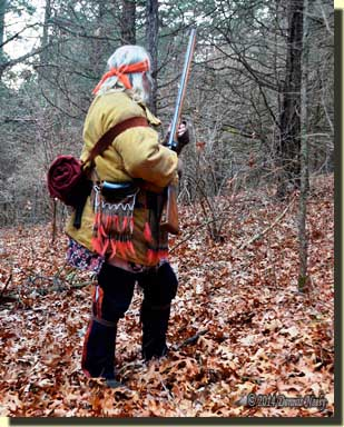 A traditional hunter still-hunting through the woods.