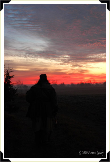 A lady of the woods silhouetted against an orange sunrise.