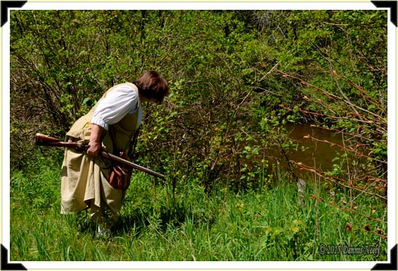 A lady of the forest checks for tracks in the mud beside the Pigeon River.