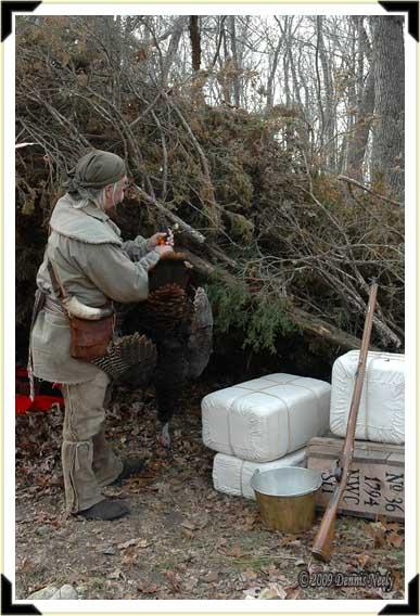 A traditional woodsman hangs a wild turkey from the cedar-brush camp's ridge pole.
