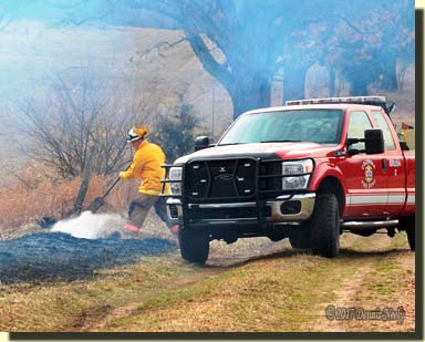 Shrouded in white smoke, a firefighter brooms out a wildfire.