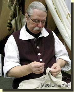 Dennis hand-sewing a linen trade shirt.