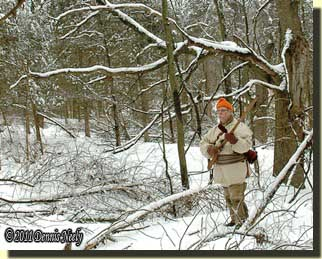 A traditional hunter wanders through the winter forest.