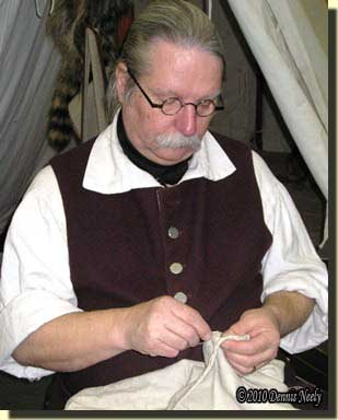 Back-stitching a French seam on an 18th-century linen hunting shirt.