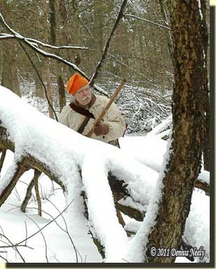 A traditional woodsman pausing behind a snow-covered deadfall.