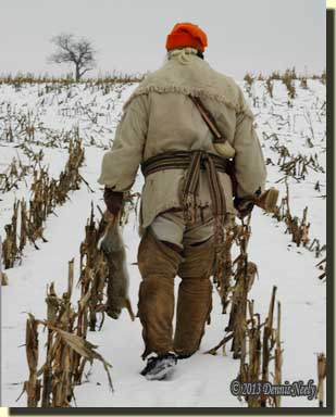 A traditional woodsman carries a rabbit as he walks down a corn row.