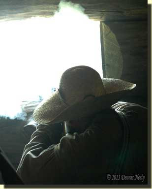 Smoke fills the window as a defender fires his 18th-century rifle.